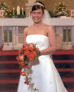 Bride at the alter with wedding flowers